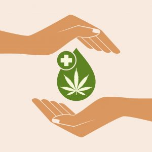 Hand holding oil drop with a marijuana leaf.